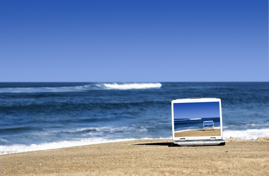 Open laptop on a beautiful beach with a great blue sky
